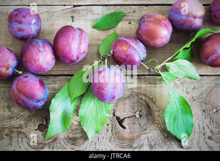 Viola fresca prugne su legno tavolo rustico