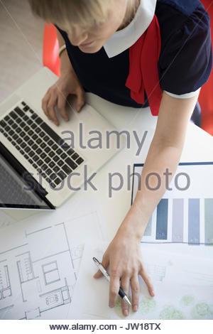 Vista aerea architetto femmina rivedendo blueprint al laptop Foto Stock