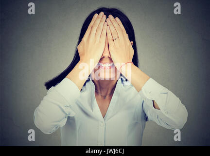Ritratto di una donna sorridente che copre i suoi occhi isolati su sfondo grigio Foto Stock