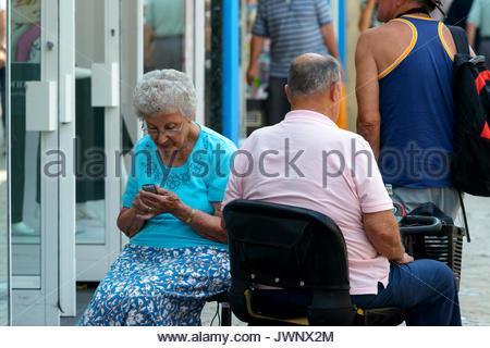OAP giovane shopping sulla mobilità scooter, Poole, Dorset, England, Regno Unito Foto Stock