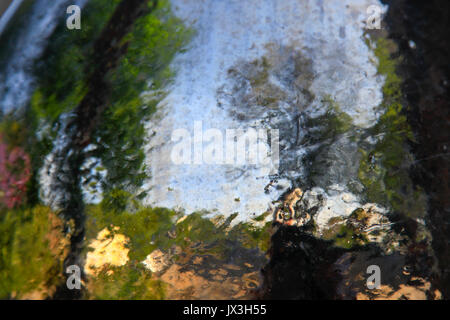 All'aperto sfocati Abstract fotografato attraverso il vetro bagnato