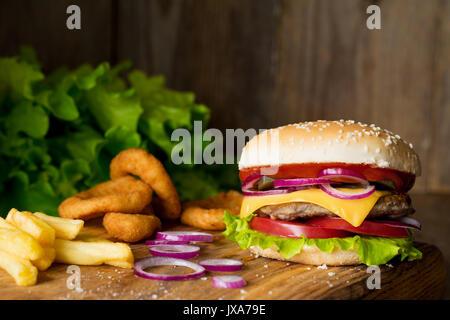 Cheeseburger, patatine fritte e anelli di cipolla sul tagliere di legno su sfondo di legno. Vista ingrandita, il Foto Stock