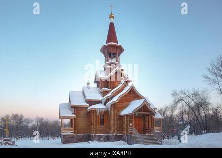 Ortodossa in legno tempio cristiano esterno in inverno nella foresta. Foto Stock