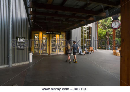 Coppia giovane camminando verso l'entrata di REI flagship store a Seattle, King County, Washington, Stati Uniti Foto Stock