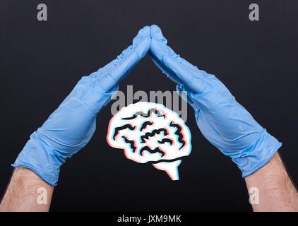 Le mani con guanti medicali a proteggere un cervello come concetto di alzheimer Foto Stock