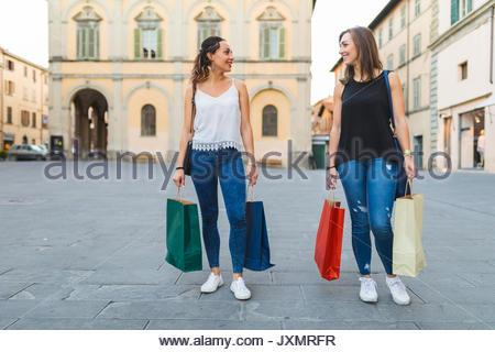 Giovani donne il trasporto delle borse della spesa in città Foto Stock