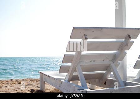 Immagine di un legno bianco sedia sole sul mare di sabbia per esterno Foto Stock