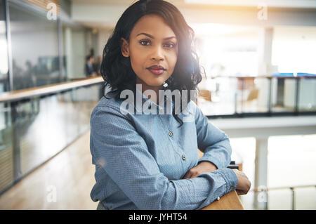 Ritratto di un attraente giovane imprenditrice cercando focalizzato mentre appoggiato su di una ringhiera nel corridoio Foto Stock
