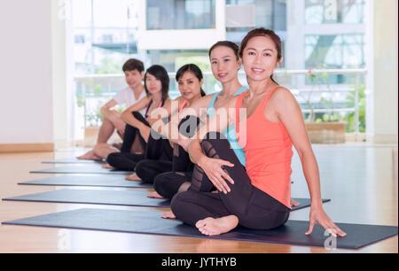 Classe di yoga in camera studio,gruppo di persone facendo seduto a metà il signore dei pesci pone ,relax benessere Foto Stock