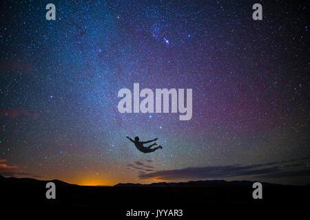 Ragazzo salti in aria al tramonto con le stelle Foto Stock