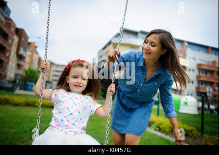 Giovane madre svolge nel parco giochi con la figlia piccola. La donna scuote il bambino su altalena. Città cortile. Foto Stock