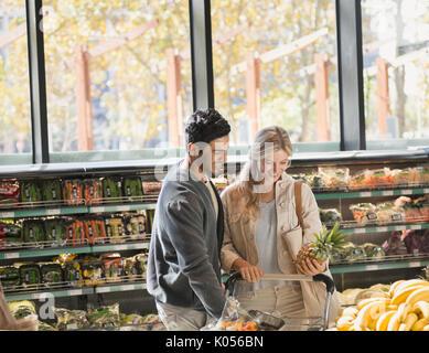 Sorridente coppia giovane la spesa tenendo ananas nel mercato Foto Stock