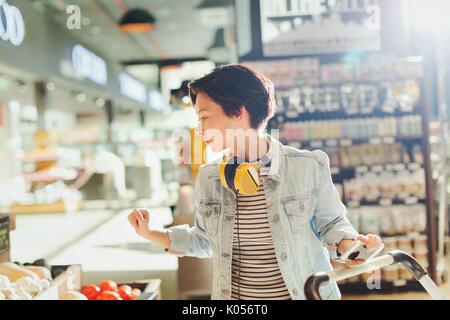 Giovane donna con le cuffie la navigazione, a fare la spesa nel mercato Foto Stock