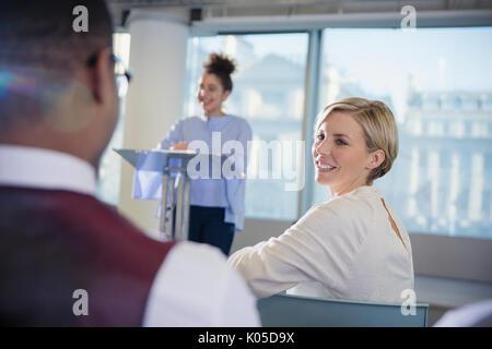 Sorridente imprenditrice di tornitura e ascolto di imprenditore nel pubblico di conferenza Foto Stock