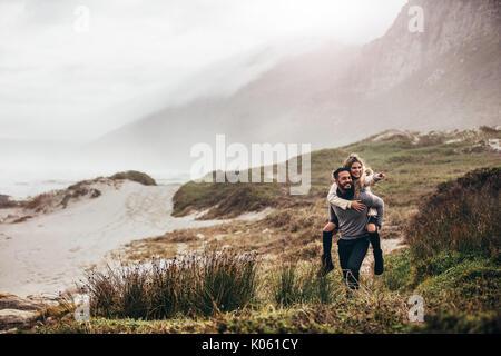 Colpo all'aperto dell'uomo che donna piggyback sulla spiaggia invernale. Uomo Donna portante oh la schiena rivolta Foto Stock