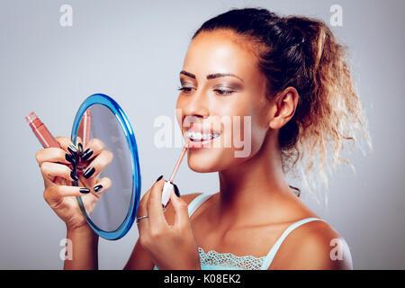 Sorridente giovane donna con bretelle applicando lip gloss sulle labbra di fronte a specchio. Foto Stock