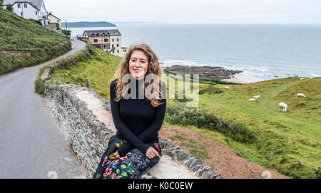 Una bella giovane donna in vacanza, seduto su un muro di pietra in Mortehoe, vicino alla baia di Woolacombe, Devon, Foto Stock