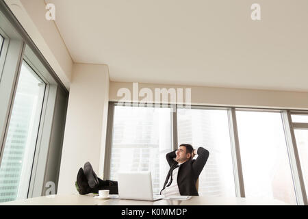 Imprenditore di relax presso un ufficio con piedi sulla scrivania, copyspace Foto Stock