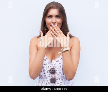Scioccato e sorpreso ragazza urlando che copre la bocca le mani . capelli ricci donna stupiti .bellissima ragazza Foto Stock