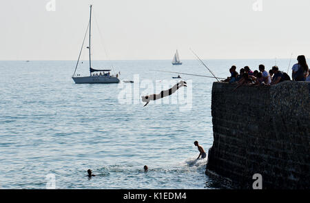 Brighton, Regno Unito. Il 27 agosto, 2017. I ragazzi del salto nel mare da un groyne sulla spiaggia di Brighton Foto Stock