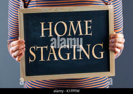 Mani femminili azienda piccola lavagna nera nella parte anteriore del corpo closeup con parole Home Staging. Su uno sfondo grigio con spazio di copia