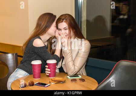 Due belle donne di bere il caffè mug, spettegolare e chattare in un cafe bar. Due ragazze seduta in una caffetteria, Foto Stock