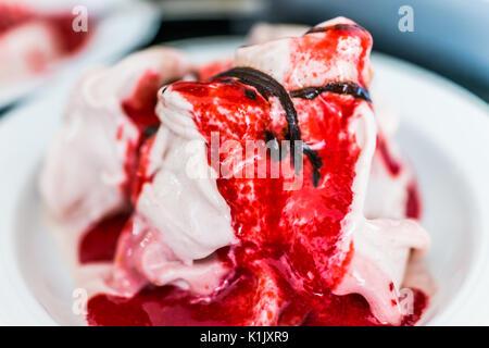 Servire morbido gelato alla vaniglia con rosso salsa di fragole e una spruzzata di sciroppo al cioccolato closeup Foto Stock