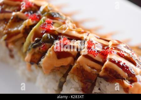 Primo piano artistico di sushi drago rosso rotolo con salmone e caviale Foto Stock