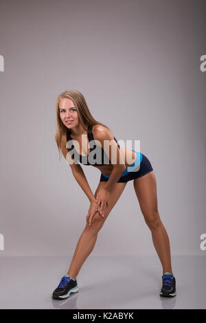 A piena lunghezza shot di montare la giovane donna facendo stretching in studio. Foto Stock