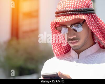 Uomo arabo utilizza lo smartphone all'aperto della città moderna Foto Stock