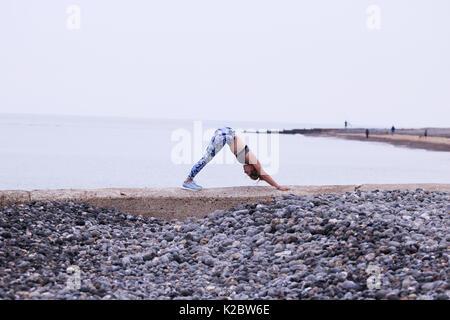 Giovane donna fare yoga sulla parete del mare a Cromer, Norfolk, Regno Unito.