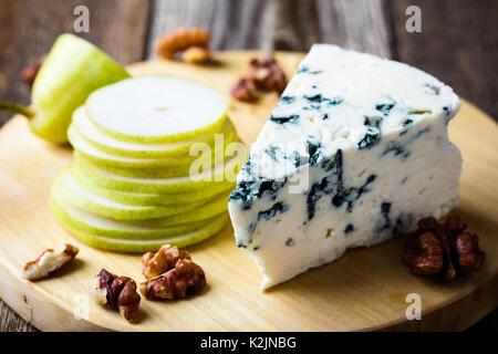 Vassoio di formaggi. Formaggio blu con pera fresco rustico di legno Foto Stock