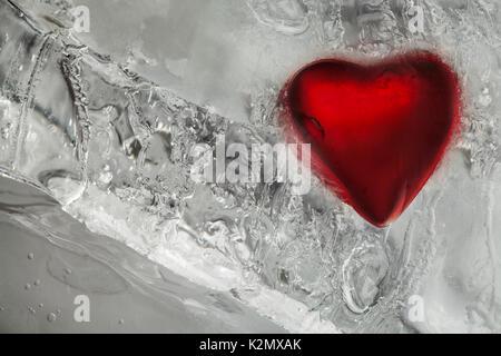 Amore congelato il cuore in ghiaccio. Il colore rosso e il gelo textured pattern. Il giorno di San Valentino, freddo inverno sfondo. Vista Macro. Foto Stock