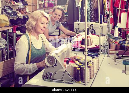 Due attraenti di tutte le età la cucitura con attrezzature professionali all'atelier Foto Stock