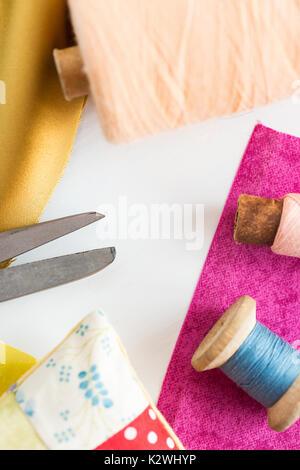 La cucitura, patchwork, sartoria e concetto di moda - strumenti di primo piano su bianco scrivania in studio, forbici, bobine di blu e rosa thread, Puntaspilli, pezzi del mosaico colorato tessuto, verticale.