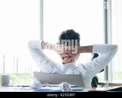 Imprenditore concetto rilassante: imprenditore seduto con i piedi fino alla scrivania in ufficio guardando fuori Foto Stock