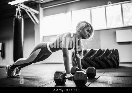 Attraente giovane donna sta facendo esercizio di tavoloni mentre si lavora in palestra Foto Stock