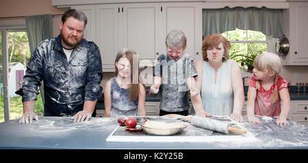 Un arrabbiato in cucina dopo una lotta di cibo e la cottura di una torta di mele. Foto Stock