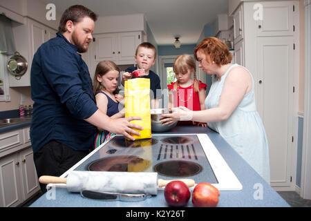 Una famiglia di cinque persone la cottura della torta di mele in cucina. Foto Stock