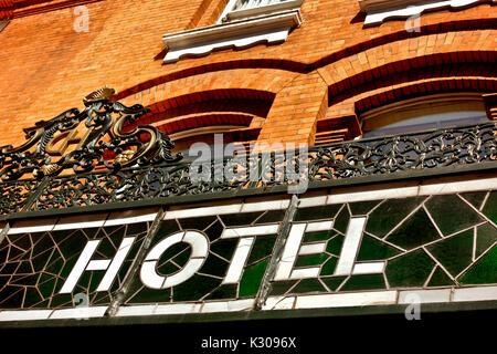 Retro in vetro colorato segno presso il Central Hotel, esterno. Mattoni rossi facciata di edificio. Destinazioni Foto Stock