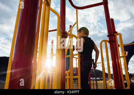 Un bambino gioca su attrezzature per parchi giochi al tramonto. Foto Stock