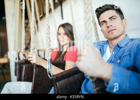 Ritratto di giovane seduto in altalene Foto Stock
