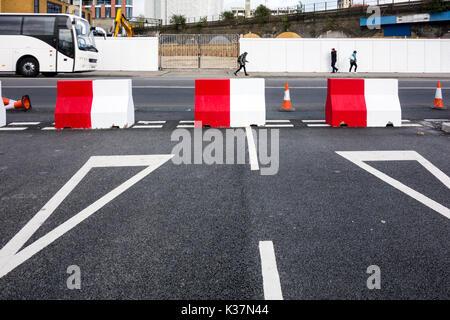 Il bianco e il rosso di blocchi in calcestruzzo su un nodo stradale bloccare una strada Foto Stock