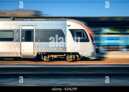 Treno ad alta velocità in movimento con la stazione ferroviaria al tramonto in Europa. Moderno treno intercity sulla piattaforma ferroviaria con motion blur effetto. In movimento Foto Stock