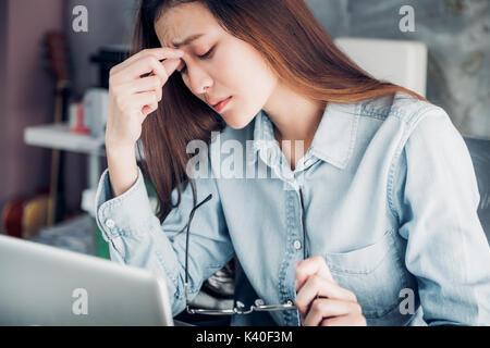 Sottolineato Asian creative designer donna coprire il suo volto con la mano e sento sconvolto dal lavoro nella parte Foto Stock