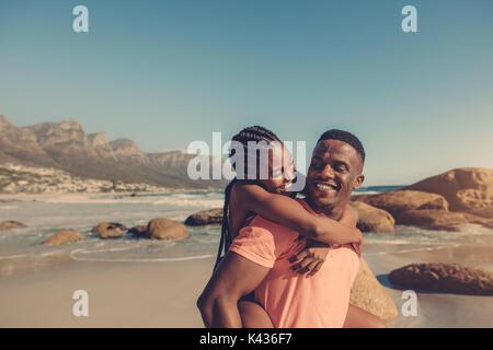 Bello l'uomo africano dando piggyback ride per la sua ragazza sorridente in spiaggia. Giovane che si diverte in riva al mare. Foto Stock