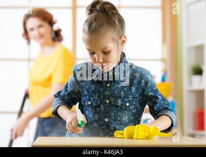 La famiglia felice pulisce la camera. La madre e il figlio di lei figlia fare pulizia in casa. Una donna e un capretto piccolo ragazza asciugò il polvere e aspirato th Foto Stock