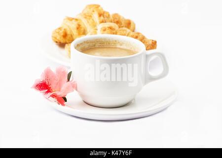 Caffè, fiore e i croissant su sfondo bianco Foto Stock