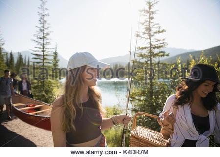 Amici di sesso femminile che porta canne da pesca, cestino da picnic e canoa lungo la soleggiata estate lago Foto Stock