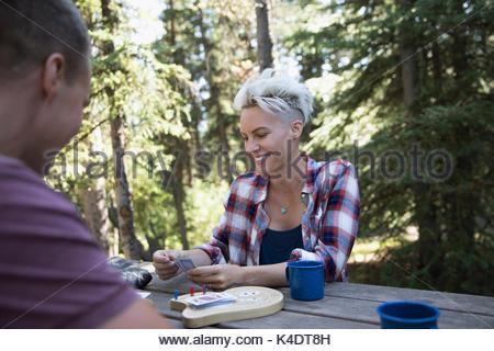 Coppia sorridente playing cribbage al campeggio tavolo da picnic nei boschi Foto Stock
